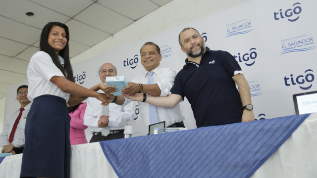 Pupil Nataly Daniela Lara Avilés receives a tablet from Vice President Oscar Ortiz and Tigo General Manager Marcelo Alemán
